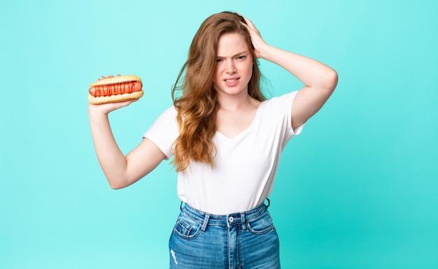 Roodharige mooie vrouw die zich gestrest, angstig of bang voelt, met de handen op het hoofd en een hotdog vasthoudt