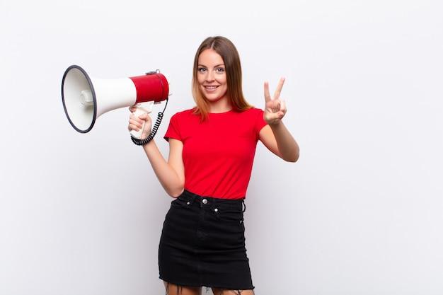 Roodharige mooie vrouw glimlacht en kijkt gelukkig, zorgeloos en positief, gebaren overwinning of vrede met één hand met een megafoon