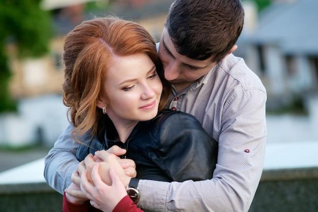 Roodharige mooie vrouw in knuffels van knappe brunette man, romantisch moment