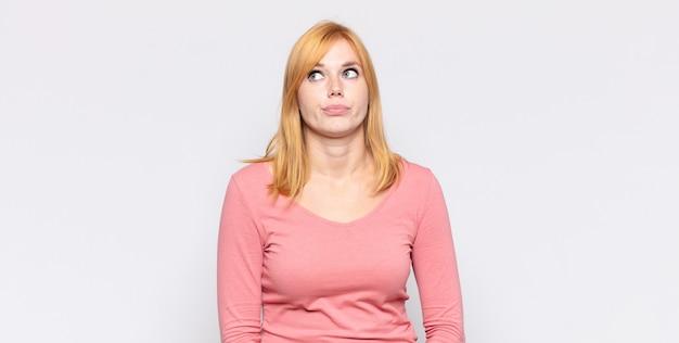 Roodharige mooie vrouw op zoek goofy en grappig met een dwaze schele uitdrukking, een grapje en gek rond