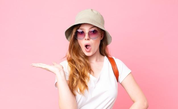 Roodharige, mooie vrouwelijke toerist die verrast en geschokt kijkt, met open mond terwijl ze een object vasthoudt