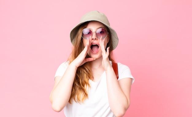 Roodharige, mooie vrouwelijke toerist die zich gelukkig voelt, een grote schreeuw geeft met de handen naast de mond