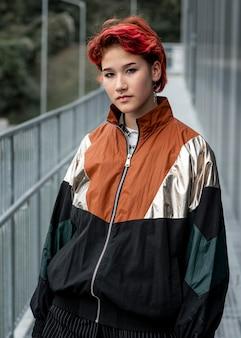 Roodharige niet-binaire persoon die buiten sportkleding draagt