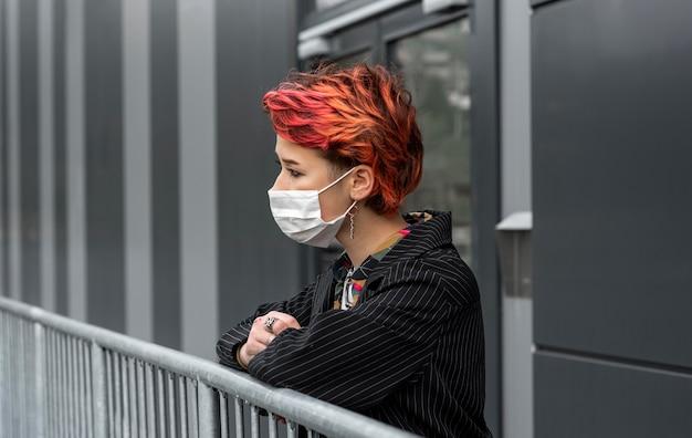 Roodharige niet-binaire persoon die buitenshuis een medisch masker draagt