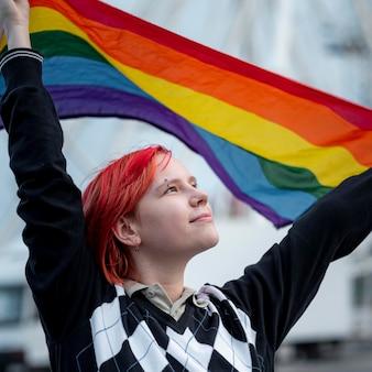 Roodharige niet-binaire persoon die een holebi-vlag omhoog houdt