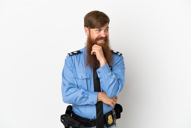 Roodharige politie man geïsoleerd op een witte achtergrond op zoek naar de kant