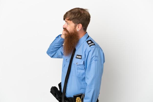 Roodharige politieman geïsoleerd op een witte achtergrond die een gesprek voert met de mobiele telefoon met iemand