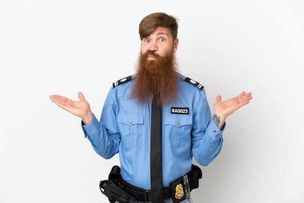Roodharige politieman geïsoleerd op een witte achtergrond die twijfels heeft terwijl hij zijn handen opsteekt
