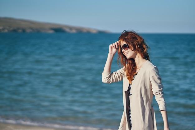 Roodharige reiziger in een jas en een t-shirt op het strand in de buurt van de zomervakantie aan zee