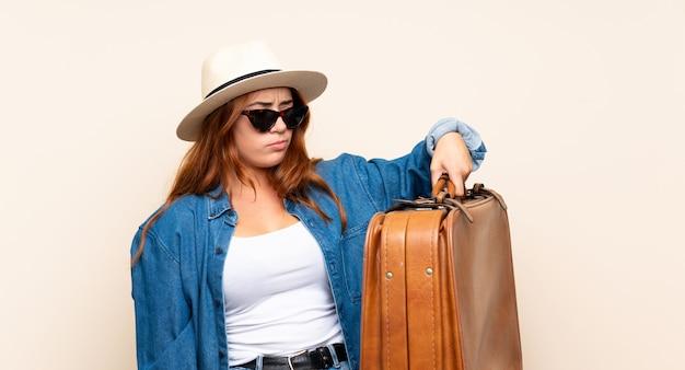 Roodharige reiziger meisje met koffer met droevige uitdrukking