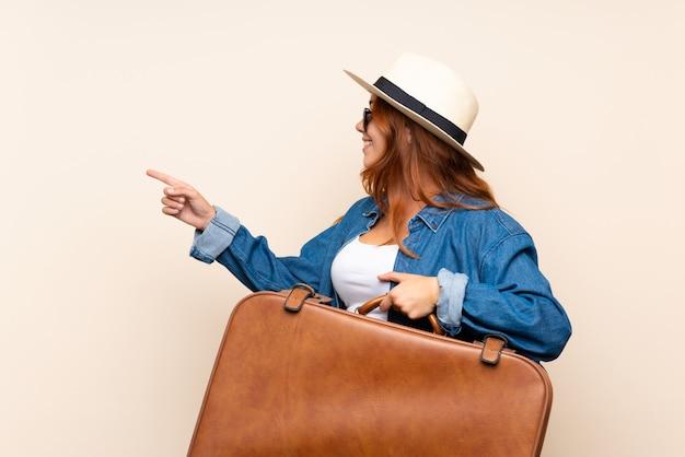 Roodharige reiziger meisje met koffer wijst naar de zijkant om een product te presenteren