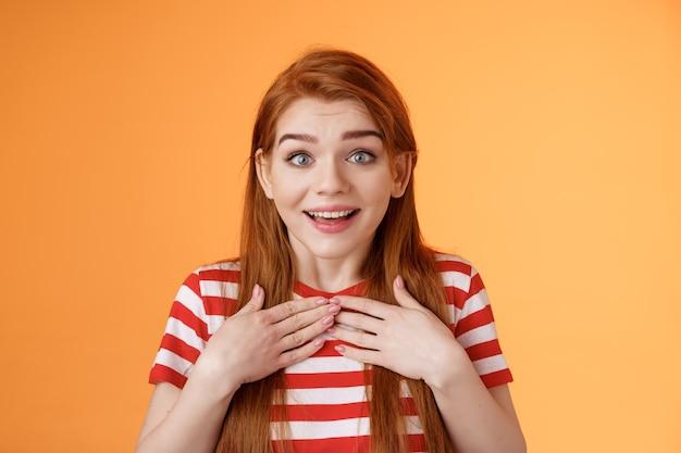 Roodharige schattig meisje ontvangt aangenaam nieuws. gecharmeerde gelukkige gembervrouw drukt handen op de borst verbaasd verrast, kijk camera verrukt, waardeer geschenk, blik dankbaar bewondering, oranje achtergrond