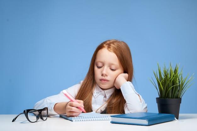 Roodharige schoolmeisje zit aan de tafel en maakt huiswerk