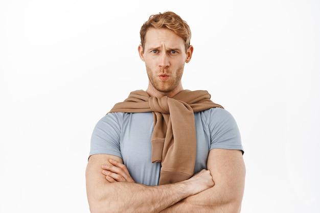 Roodharige sterke sportieve man fronst en krimpt ineen, reageert op iets ongemakkelijks of ongemakkelijks, ziet een pijnlijk ding, kruist armen op de borst, kijkt naar slecht cringy ding, witte muur