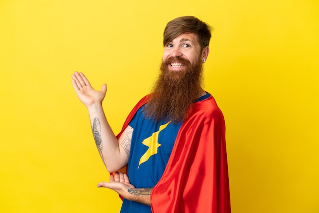 Roodharige super hero-man geïsoleerd op een gele achtergrond die zijn handen naar de zijkant uitstrekt om uit te nodigen om te komen