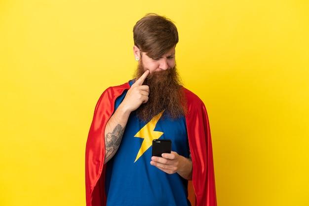 Roodharige super hero man geïsoleerd op gele achtergrond denken en een bericht verzenden