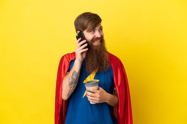 Roodharige super hero man geïsoleerd op gele achtergrond met koffie om mee te nemen en een mobiel
