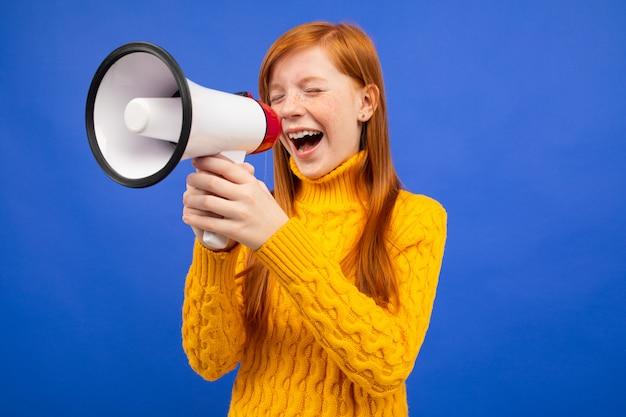 Roodharige tiener die met gesloten ogen aan de nieuwsluidspreker gilt op een blauwe studioachtergrond