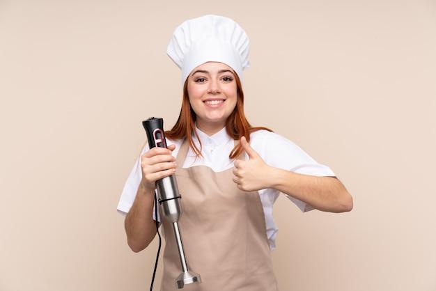 Roodharige tiener meisje met behulp van staafmixer over met duimen omhoog omdat er iets goeds is gebeurd