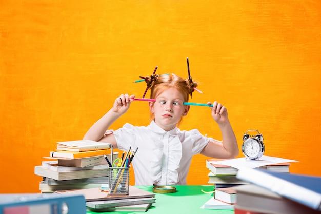 Roodharige tiener meisje met veel boeken thuis