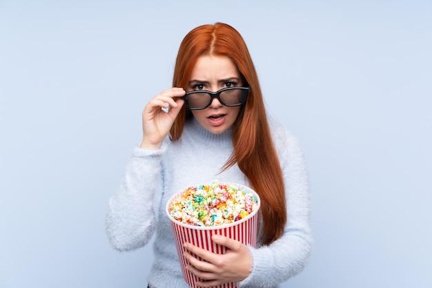 Roodharige tiener meisje over geïsoleerde blauwe muur verrast met 3d-bril en houden een grote emmer popcorns