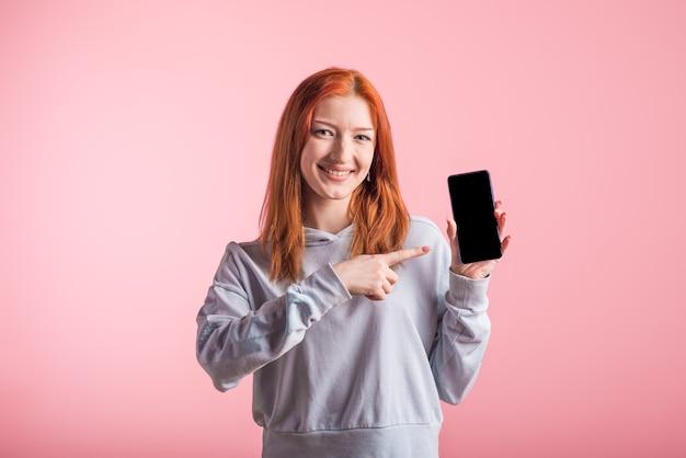 Roodharige tiener meisje wijst met vinger op het lege scherm van de smartphone in de studio op roze achtergrond