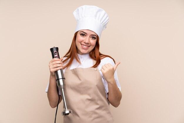 Roodharige tiener vrouw met behulp van staafmixer wijzend naar de zijkant om een product te presenteren