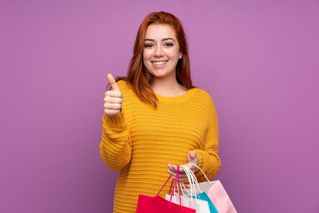 Roodharige tiener vrouw met boodschappentassen en met duim omhoog