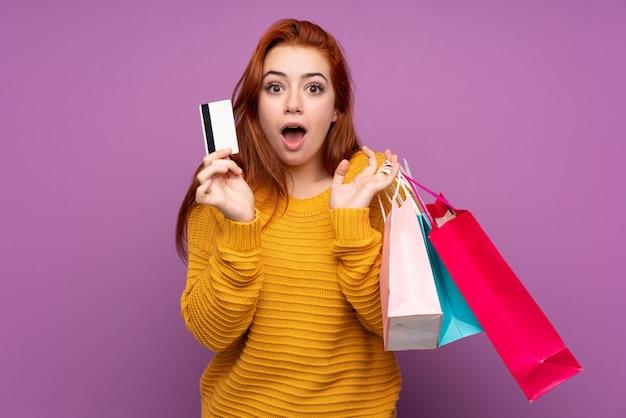 Roodharige tiener vrouw met boodschappentassen en verrast