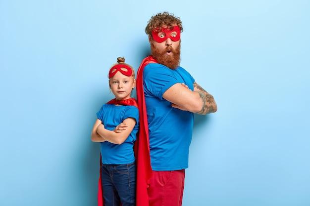 Roodharige vader en dochter spelen samen een superheldenspel, staan achterover, veel plezier