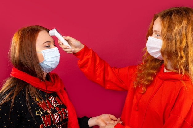 Roodharige vriendinnen in medische maskers meten hun lichaamstemperatuur met een contactloze thermometer. foto op een rode muur. virus en pandemie concept.