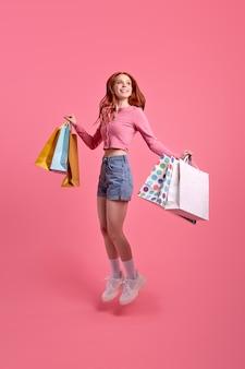Roodharige vrolijke mooie grappige funky dame die pakketten vasthoudt, geniet van het winkelen, gekleed in lichtgekleurde...