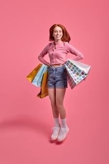 Roodharige vrolijke mooie grappige funky dame die pakketten vasthoudt, geniet van verheugen winkelen gekleed lichtgekleurde moderne kleding geïsoleerd trendy kleurrijke roze achtergrond in studio