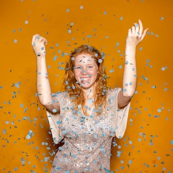Roodharige vrouw confetti gooien