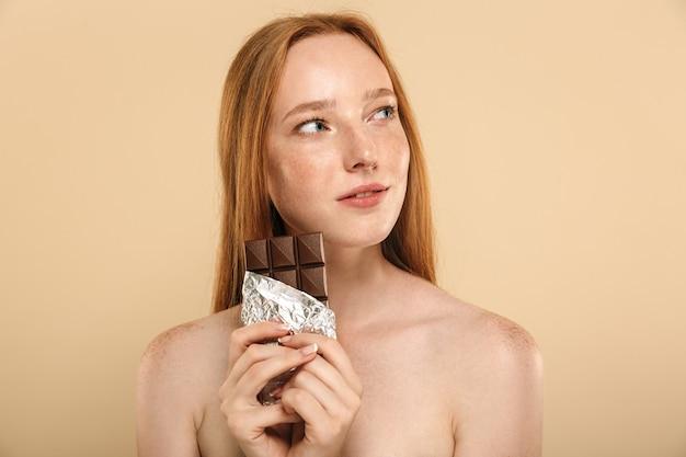 Roodharige vrouw die chocolade eet.