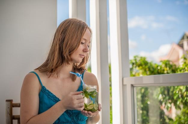 Roodharige vrouw die een mojito drinkt op het terras