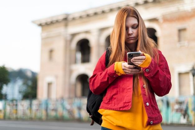 Roodharige vrouw die haar telefoon controleert
