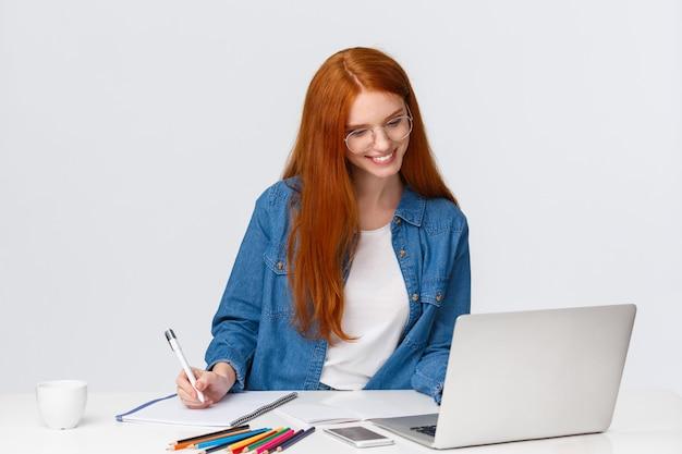 Roodharige vrouw die in glazen iets van laptop leest