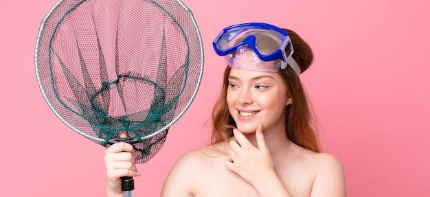 Roodharige vrouw die lacht met een gelukkige, zelfverzekerde uitdrukking met de hand op de kin met een bril en een visnet