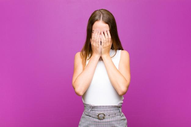 Roodharige vrouw die verdrietig, gefrustreerd, nerveus en depressief is, kegelvormig gezicht met beide handen, huilend op paarse muur