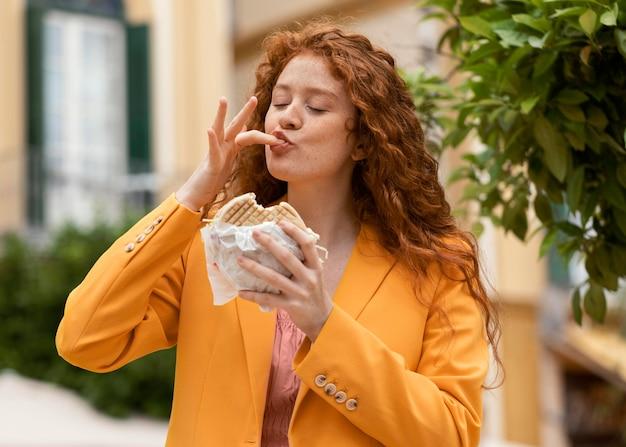 Roodharige vrouw die wat straatvoedsel eet