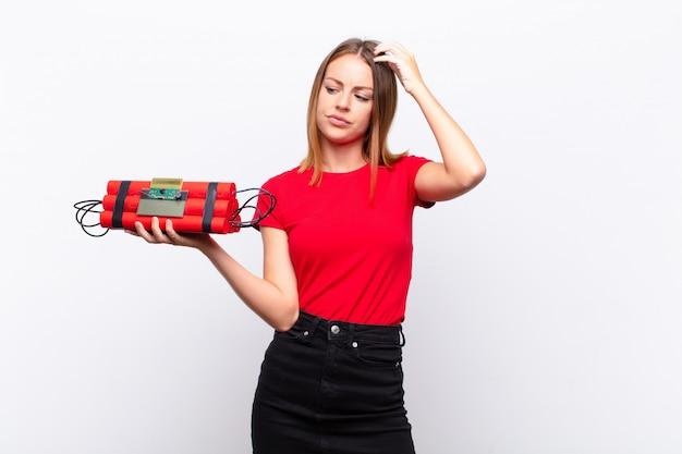 Roodharige vrouw die zich verbaasd en verward voelt, haar hoofd krabt en opzij kijkt met een dynamietbom