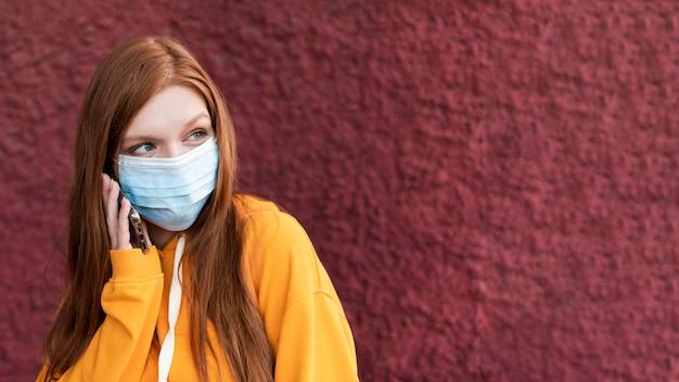 Roodharige vrouw draagt een gezichtsmasker met kopie ruimte