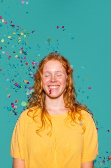 Roodharige vrouw feesten met confetti