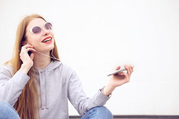 Roodharige vrouw gekleed in hoody, jeans en rode sneakers, met rode lippenstift geschilderde lippen luisteren naar muziek in smartphone in zonnige zomerdag en plezier