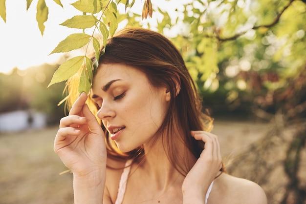 Roodharige vrouw in de buurt van boomgroene bladeren charme van de zomer