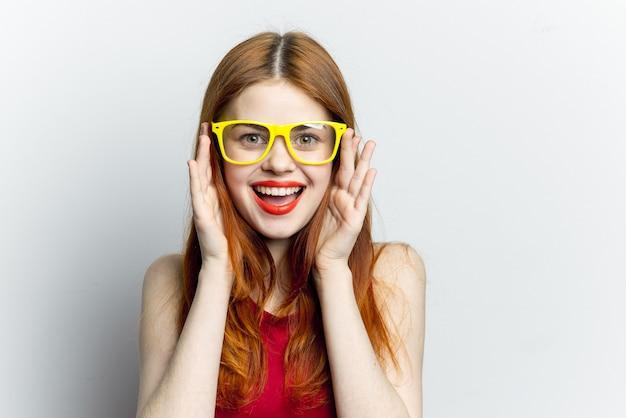 Roodharige vrouw in een rode jurk en gele glazen, wit