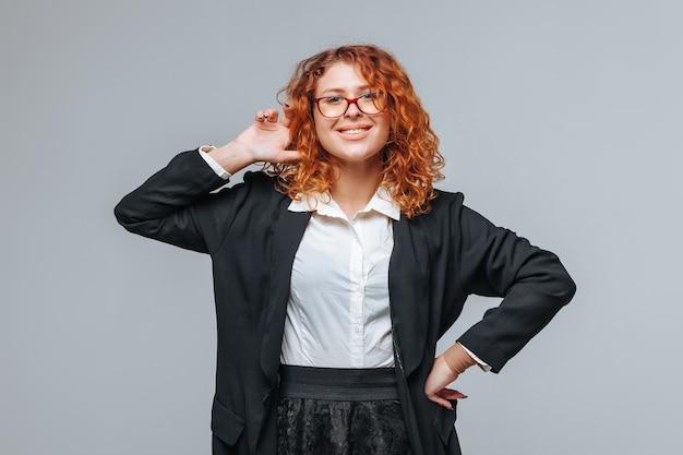 Roodharige vrouw in een zwarte jas en glazen glimlachen