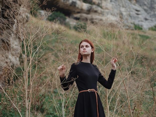 Roodharige vrouw in een zwarte jurk lopen op de natuur in de herfst in het bos
