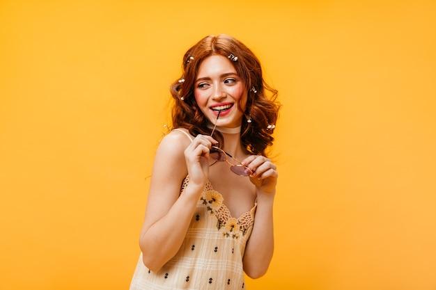 Roodharige vrouw in geruite jurk glimlacht en bijt sluiting van zonnebril op gele achtergrond.